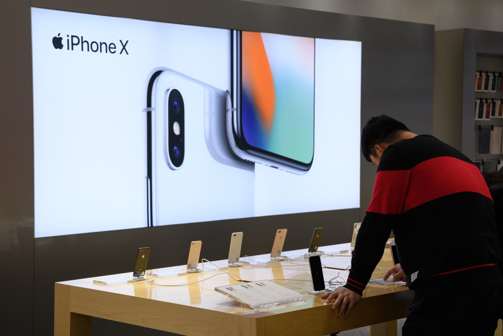 A customer looks at an Apple Inc. iPhone X at a SoftBank Group Corp. store in Tokyo, Japan, on Thursday, Feb. 22, 2018. Billionaire founderMasayoshi Sonsaidthis month that the company will start preparing for the mobile IPO and aims for a listing within a year. It could still end up scrapping the plan, the company said on Feb. 7. Photographer: Akio Kon/Bloomberg via Getty Images