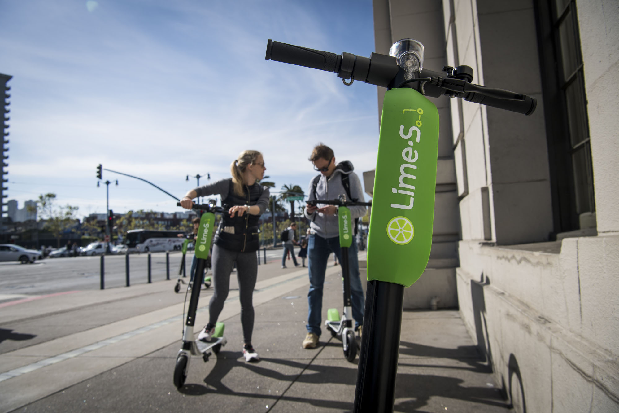 People use a smartphone to LimeBike shared electric scooters on the Embarcadero in San Francisco. MUST CREDIT: Bloomberg photo by David Paul Morris.