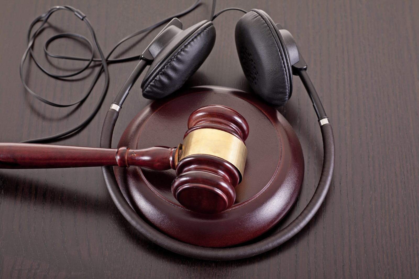 Concept image about music piracy and copyright protection law featuring  a gavel and headphones on tabletop