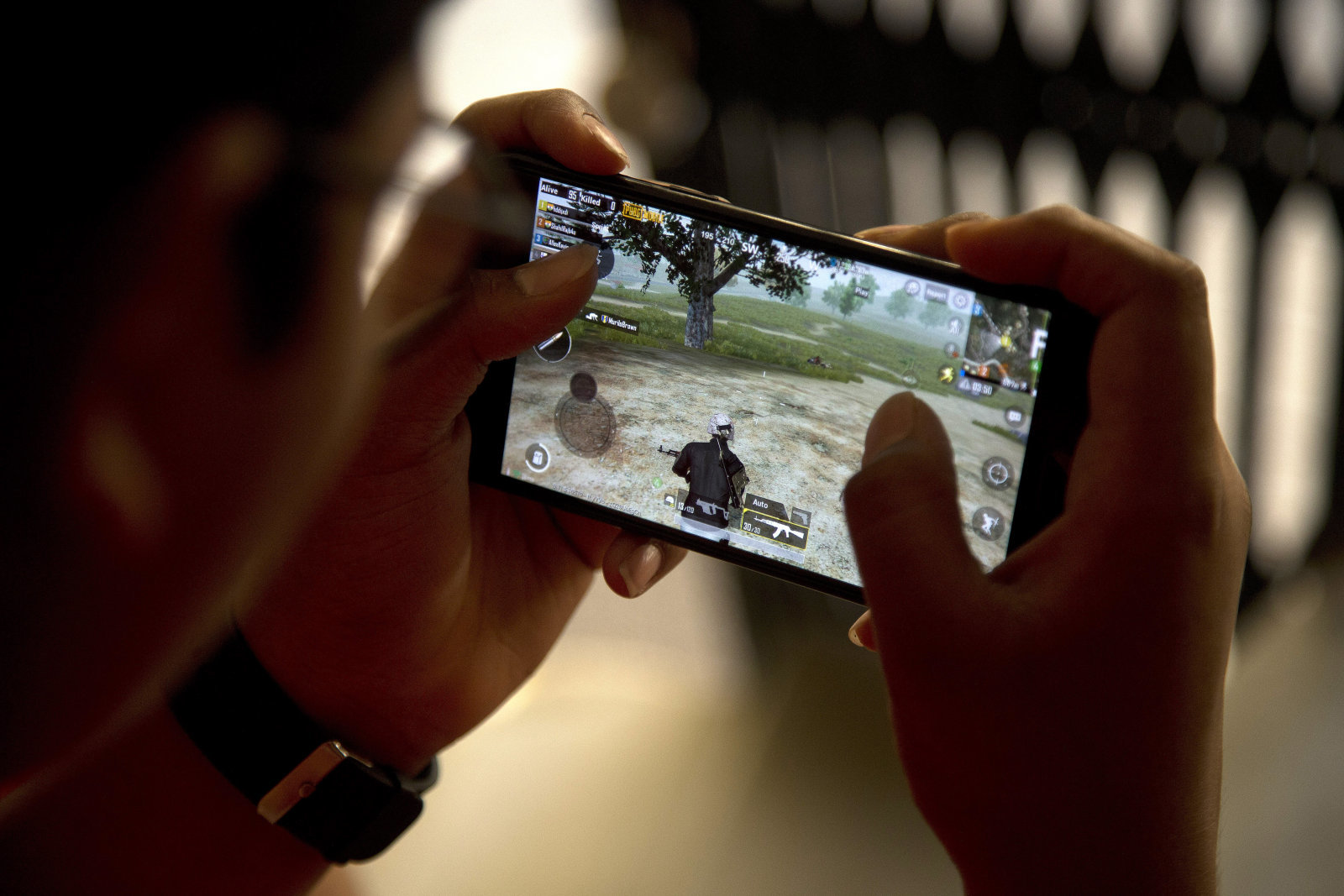 An Indian boy plays an online game PUBG on his mobile phone sitting outside his house  in Hyderabad, India, Friday, April 5, 2019. A boy's suicide in India after his mother scolded him for playing the popular online game PlayerUnknown's Battlegrounds has inflamed a debate across the country over whether the game should be banned. (AP Photo/ Mahesh Kumar A.)