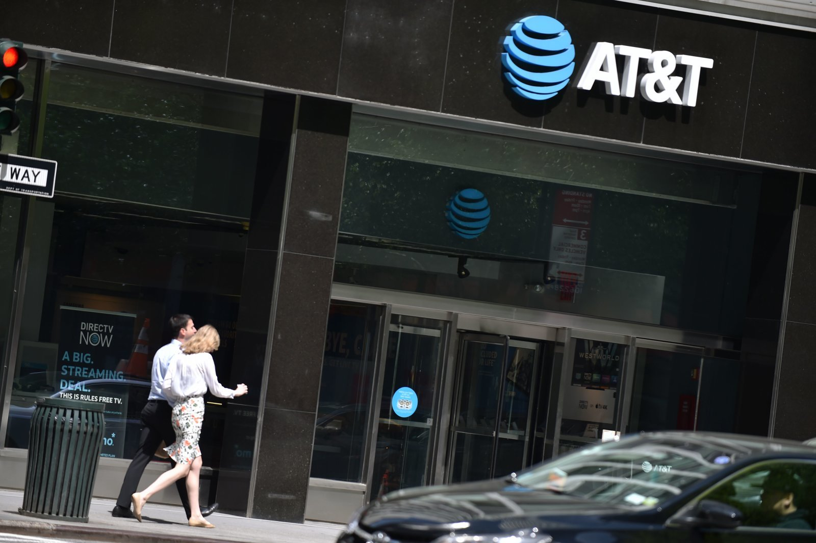 People walk by an AT&T store in New York City, on May 11, 2018. (Photo by HECTOR RETAMAL / AFP)        (Photo credit should read HECTOR RETAMAL/AFP/Getty Images)