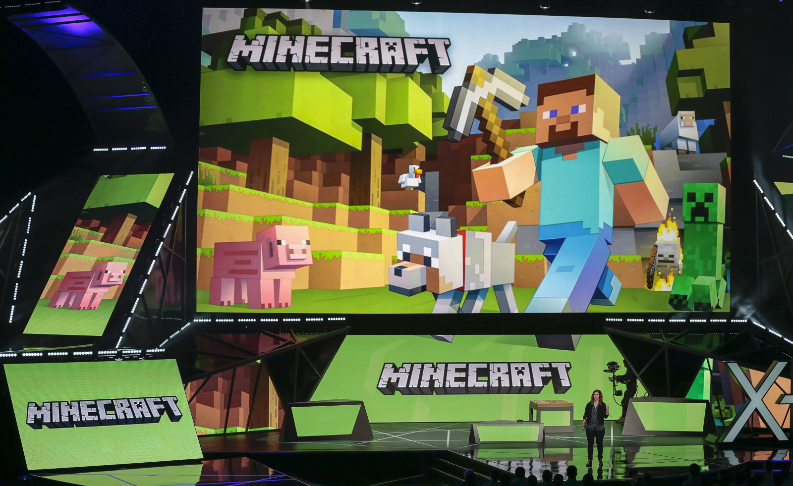 """FILE - In this June 15, 2015 file photo, Lydia Winters, at podium, shows off Microsoft's """"Minecraft"""" built specifically for HoloLens during a live demo at the Xbox E3 2015 briefing ahead of the Electronic Entertainment Expo at the University of Southern California's Galen Center in Los Angeles.The maker of Windows operating systems and Xbox game consoles constructed a $2.5 purchase of """"Minecraft"""" developer Mojang in 2014. Microsoft quickly begun incorporating the brick-building game series into its new products with the release of a Windows 10 edition of """"Minecraft,"""" as well as demonstrating an augmented reality rendition for use with its prototype HoloLens headset at industry trade events in 2015. (AP Photo/Damian Dovarganes, File)"""