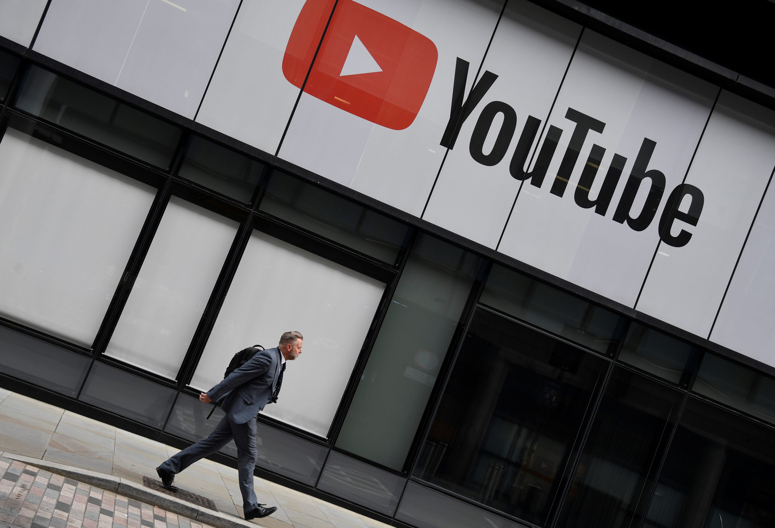 A worker walks past YouTube offices, in King's Cross, London, Britain, September 11, 2020. REUTERS/Toby Melville - RC2CWI99MPBH